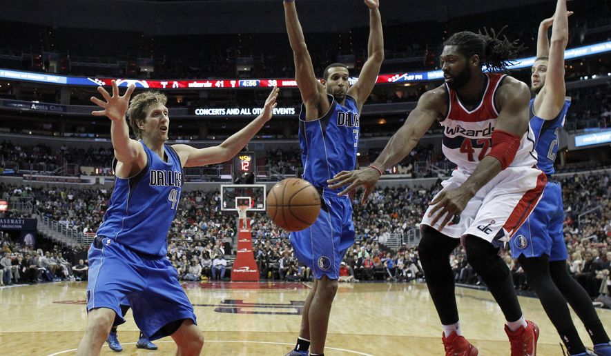 Washington Wizards forward Nene (42) passes the ball as he guarded by Dallas Mavericks forward Dirk Nowitzki, left, forward Brandan Wright and forward Chandler Parsons, right, during the first half of an NBA basketball game, Wednesday, Nov. 19, 2014, in Washington. The Mavericks won 105-102. (AP Photo/Alex Brandon)