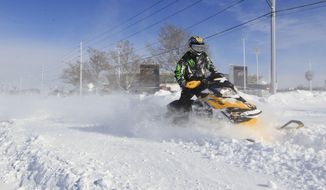 A snowmobiler makes his way down Abbott Road in front of Ralph Wilson Stadium,  home of the Buffalo Bills,  in Orchard Park, N.Y. on  Wednesday, Nov. 19, 2014.  A ferocious lake-effect storm left the Buffalo area buried under 6 feet of snow Wednesday, trapping people on highways and in homes, and another storm expected to drop 2 to 3 feet more was on its way. (AP Photo/The Buffalo News, Harry Scull Jr.)  TV OUT; MAGS OUT; MANDATORY CREDIT; BATAVIA DAILY NEWS OUT; DUNKIRK OBSERVER OUT; JAMESTOWN POST-JOURNAL OUT; LOCKPORT UNION-SUN JOURNAL OUT; NIAGARA GAZETTE OUT; OLEAN TIMES-HERALD OUT; SALAMANCA PRESS OUT; TONAWANDA NEWS OUT