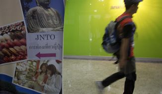 """In this Nov. 19, 2014 photo, a Thai man walks near a billboard of a tour in Japan, outside Japan National Tourism Organization office in Bangkok, Thailand. Thailand's embassy in Japan has some tips for Thai visitors: Don't put your chopsticks in the serving bowl. And if driving, stop for pedestrians at cross walks. The advice is part of a new online manners guide the embassy has posted on its Facebook page in response to criticism on social media about """"inappropriate"""" behavior of Thai tourists in Japan. (AP Photo/Sakchai Lalit)"""