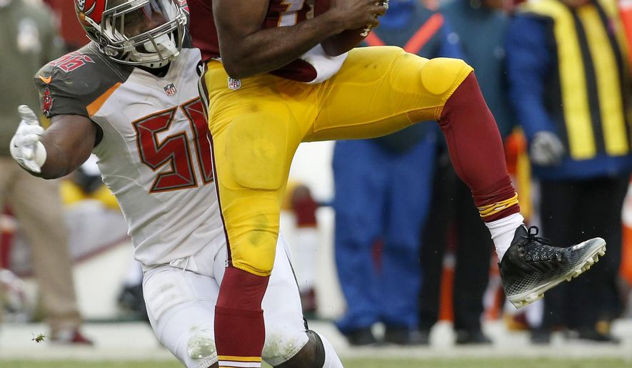 Tampa Bay Buccaneers defensive end Jacquies Smith (56) sacks Washington Redskins quarterback Robert Griffin III (10) during the second half of an NFL football game in Landover, Md., Sunday, Nov. 16, 2014. The Buccaneers defeated the Redskins 27-7. (AP Photo/Alex Brandon)