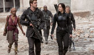 """Jennifer Lawrence stars as Katniss Everdeen with Liam Hemsworth as Gale Hawthorne in """"The Hunger Games: Mockingjay Part 1."""" There's a lot that doesn't add up in the latest entry from the first half of the final book in the series of popular young adult novels. (Lionsgate via Associated Press)"""