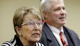 Attorney Cheryl Maples, left, speaks to reporters as her colleague Jack Wagoner listens Thursday, Nov. 20, 2014, at the Justice Building in Little Rock, Ark. The two lawyers for same-sex couples asked the Arkansas Supreme Court to reject the state's ban on gay marriage. (AP Photo/Danny Johnston)