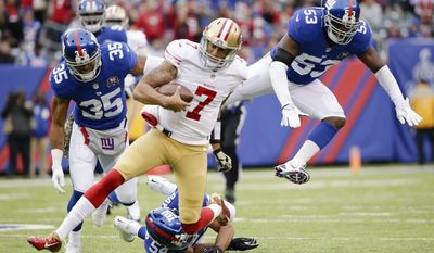 San Francisco 49ers quarterback Colin Kaepernick (7) avoids New York Giants middle linebacker Jameel McClain (53) and Quintin Demps (35) as he slides during the first half of an NFL football game Sunday, Nov. 16, 2014, in East Rutherford, N.J.  (AP Photo/Julio Cortez)