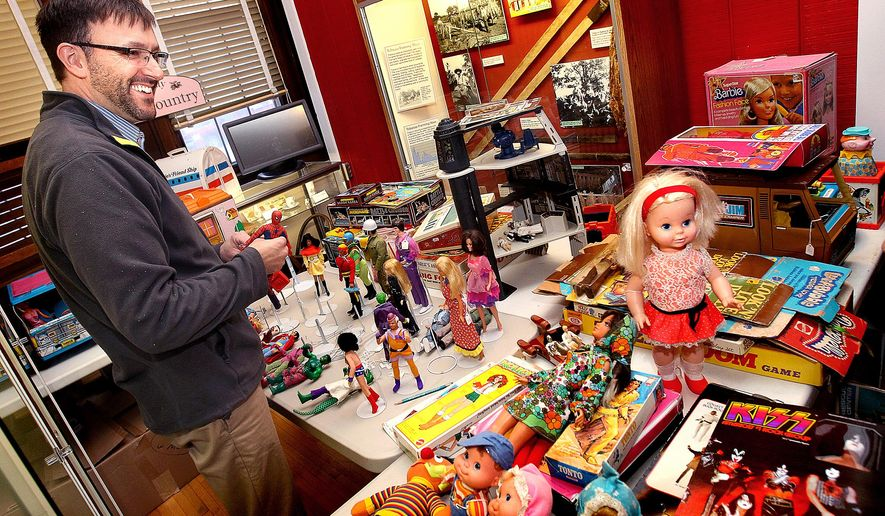 "ADVANCE FOR WEEKEND EDITIONS, NOV. 22-24 - In this Nov. 12, 2014, file photo, Monroe County Historical Society director Jarrod Roll sorts through 1970s era toys for their upcoming ""A Very 1970s Christmas"" exhibit in Sparta, Wis. (AP Photo/The La Crosse Tribune, Peter Thomson)"