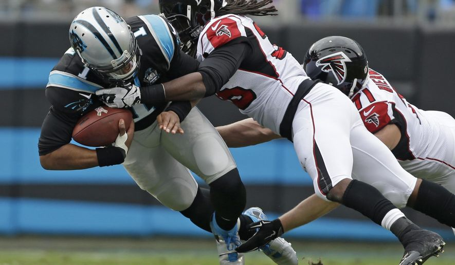 Carolina Panthers' Cam Newton (1) is sacked by Atlanta Falcons' Kemal Ishmael (36) and Kroy Biermann (71) in the first half of an NFL football game in Charlotte, N.C., Sunday, Nov. 16, 2014. (AP Photo/Bob Leverone)
