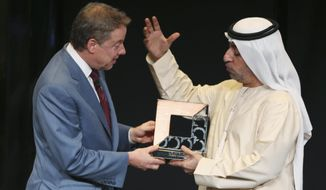 "William Clay Ford, Jr., executive chairman of Ford Motor Co. and vice chairman of the Detroit Lions, left, receives a ""Dubai Chamber of Commerce"" emblem during the ""Future of Mobility"" talk at a hotel in Dubai, United Arab Emirates, Wednesday, Nov. 19, 2014. (AP Photo/Kamran Jebreili)"