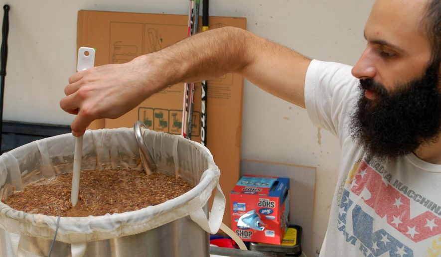 """ADVANCE FOR RELEASE MONDAY, NOV. 24, 2014, AT 12:01 A.M. CST. AND THEREAFTER - In this photo taken on Nov. 4, 2004, Cory Ellis stirs a simmering pot of beer, an ale he based on a family recipe at his home in Roscoe, Ill. Creativity can take many forms and art can come from anywhere. Ellis proves this as sunlight comes pouring into his garage and he stirs a large pot of a creative concoction that smells both nutty and a bit like wheat. """"A lot of home brewing is like kind of MacGyvering because you're piecing stuff together,"""" Ellis says as he lowers the heat on the burner while continuing to stir the mash -- grains, sweet potatoes and pecans, after a recipe his mom used to make. Ellis is in the first stages of brewing an ale based on sweet potato casserole - a hobby he shares with several people as part of the Stateline Brewing Society members.  (AP Photo/The Beloit Daily News, Jennifer Tranmer)"""