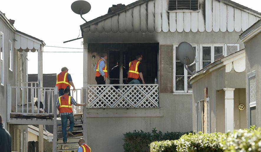 Southern California Gas Company officials enter an apartment that caught fire killing two children ages 2 and 6 in San Bernardino, Calif., Thursday, Nov. 20, 2014. The children were killed early Thursday in the California apartment fire that broke out hours after their mother went to a hospital to give birth, authorities said. The children's father was critically injured in the blaze at the two-story duplex, fire Battalion Chief Michael Bilheimer said. (AP Photo/The Sun, John Valenzuela) MANDATORY CREDIT