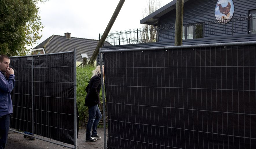 A man stands outside a fenced off area at a chicken farm where bird flu was detected in Hekendorp, central Netherlands, Monday, Nov. 17, 2014. The Dutch government has also banned the transport of poultry and eggs throughout the Netherlands after finding bird flu at a chicken farm. (AP Photo/Peter Dejong)