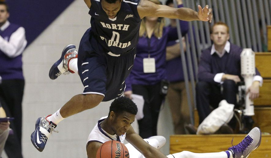 North Florida guard Jalen Nesbitt (0) and Northwestern forward Vic Law (4) battle for a loose ball during the second half of an NCAA college basketball game in Evanston, Ill., on Thursday, Nov.20, 2014. Northwestern won 69-67. (AP Photo/Nam Y. Huh)