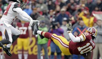 Tampa Bay Buccaneers defensive back Brandon Dixon (39) knocks down Washington Redskins quarterback Robert Griffin III (10) during the first half of an NFL football game in Landover, Md., Sunday, Nov. 16, 2014. (AP Photo/Mark Tenally)