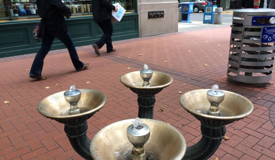 This Nov. 7, 2014 photo shows the first Benson Bubbler at the corner of Southwest Fifth and Washington in downtown Portland. Ore.  Benson Bubblers are those brass, four-bowled water fountains that you can see scattered through the downtown core. Benson Bubblers go back to 1912, when Simon Benson donated $10,000 to the city (roughly $240,000 in today's money) to purchase and install 20 of the fountains.    Engineers with the Water Bureau have struggled for decades with the question of how to balance the city's penchant for conservation with the sheer beauty of the fountains. (AP Photo/The Oregonian, John Killen)  MAGS OUT; TV OUT; NO LOCAL INTERNET; THE MERCURY OUT; WILLAMETTE WEEK OUT; PAMPLIN MEDIA GROUP OUT