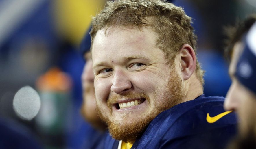 FILE - In this Nov. 16, 2014, file photo, Green Bay Packers' T.J. Lang smiles on the bench during the second half of an NFL football game against the Philadelphia Eagles in Green Bay, Wis. The Packers can't be prolific with quarterback Aaron Rodgers on the ground. The offensive line has been keeping Rodgers clean and upright lately.(AP Photo/Mike Roemer, File)