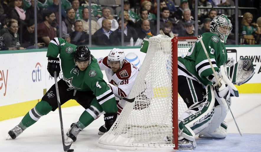 Dallas Stars goalie Kari Lehtonen (32), of Finland, minds the net as Brenden Dillon (4) clears the puck under pressure from Arizona Coyotes' Mikkel Boedker (89), of Denmark, in the second period of an NHL hockey game, Thursday, Nov. 20, 2014, in Dallas. (AP Photo/Tony Gutierrez)