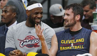 Cleveland Cavaliers forwards LeBron James, left, and Kevin Love joke with each other on the bench in the fourth quarter of the Cavaliers' 110-101 victory over the Denver Nuggets in an NBA basketball game in Denver on Friday, Nov. 7, 2014. (AP Photo/David Zalubowski)
