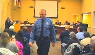In this  Feb. 11, 2014, file image from video provided by the City of Ferguson, Mo., Officer Darren Wilson attends a city council meeting in Ferguson. (AP Photo/City of Ferguson, File)