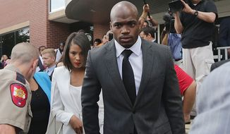 FILE - In this Oct. 8, 2014, file photo, Minnesota Vikings running back Adrian Peterson leaves court accompanied by his wife, Ashley Brown Peterson, in Conroe, Texas. The NFL suspended Adrian Peterson without pay for at least the remainder of the season. The league said Tuesday, Nov. 18, 2014, it informed the Minnesota Vikings running back he will not be considered for reinstatement before April 15 for violating the NFL personal conduct policy. (AP Photo/Houston Chronicle, Billy Smith II, File)