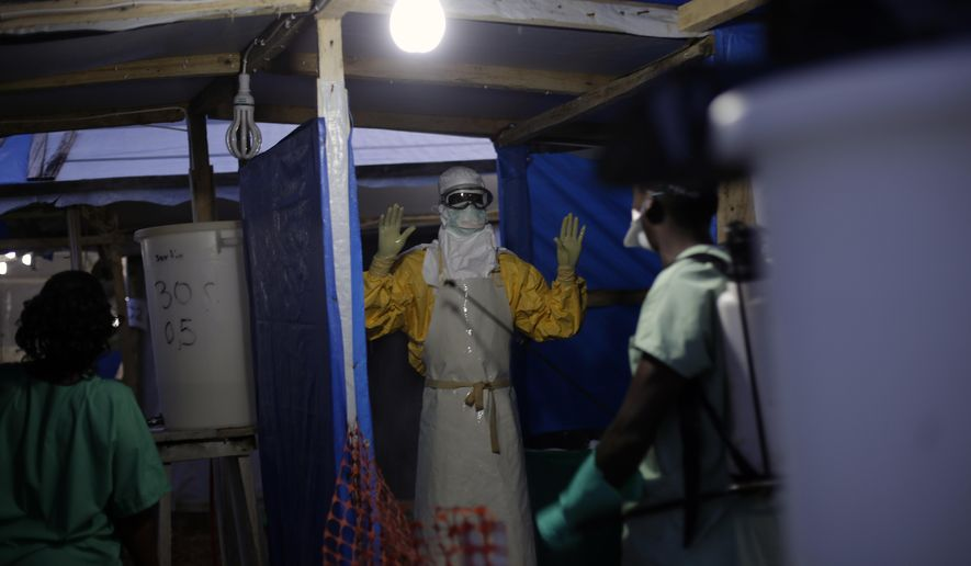 In this picture taken Thursday Nov. 20, 2014, an MSF Ebola heath worker is sprayed as he leaves the contaminated zone at the Ebola treatment centre in  Gueckedou, Guinea. Officials in Guinea say bandits during a roadside robbery stole a cooler containing blood samples that are believed to have Ebola, from a vehicle traveling from Kankan prefecture in central Guinea to a test site in Gueckedou, in the south.(AP Photo/Jerome Delay)