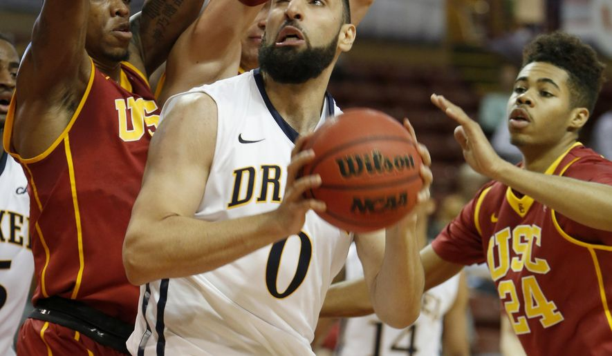 Drexel's Sooren Derboghosian, center, looks for room to shoot as Southern California's Darion Clark, left, and Malik Marquetti, right, defend during the first half of an NCAA college basketball game at the Charleston Classic tournament in Charleston, S.C., Friday, Nov. 21, 2014. (AP Photo/Mic Smith)