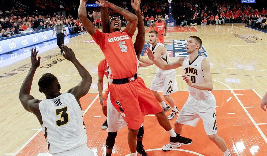 Syracuse's Chris McCullough (5) drives past Iowa's Jarrod Uthoff, right, during the first half of an NCAA college basketball game at Madison Square Garden, Friday, Nov. 21, 2014, in New York. (AP Photo/Frank Franklin II)