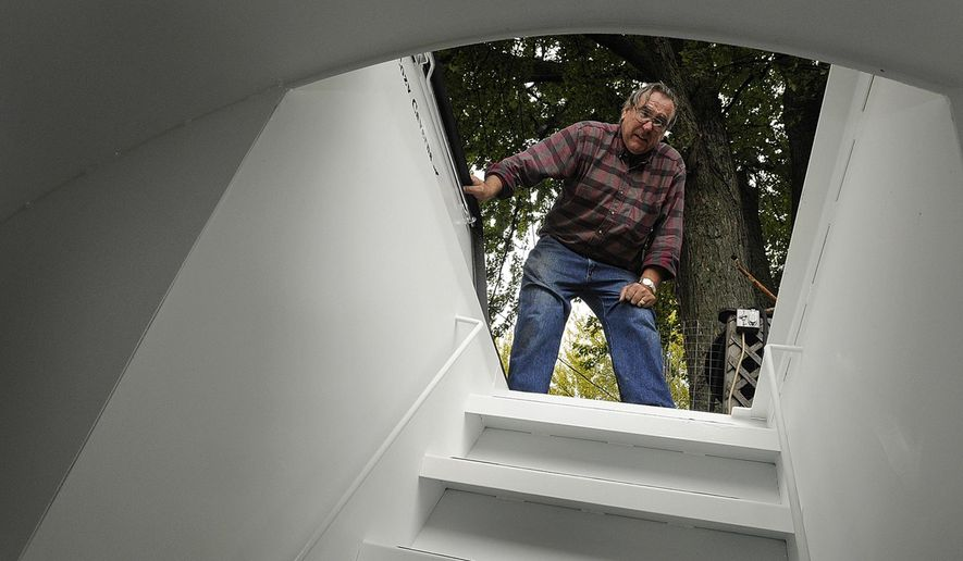 ADVANCE FOR USE SUNDAY, NOV. 23 AND THEREAFTER - In this Oct. 12, 2014 photo, Jim Trudeau looks down into the newly installed underground storm shelter in the backyard of his home in Bourbonnais, Ill. The storm shelter was a nearly $7,000 investment with all the work completed, making it a major purchase for Trudeau and his wife, Melody. The couple had wanted one for years. (AP Photo/The Daily Journal, Mike Voss)