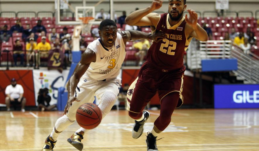 West Virginia guard Juwan Staten, left, dribbles past Boston College forward Aaron Brown at a NCAA college basketball game in San Juan, Puerto Rico, Friday, Nov. 21, 2014. (AP Photo/Ricardo Arduengo)