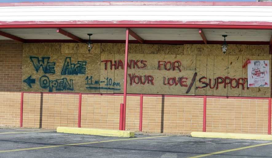 A message on an open but boarded up business thanks people for their support Thursday, Nov. 20, 2014, in Ferguson, Mo. Ferguson and the St. Louis region are on edge in anticipation of the announcement by a grand jury whether to criminally charge Officer Darren Wilson in the killing of 18-year-old Michael Brown. (AP Photo/Jeff Roberson)