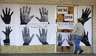 A man who declined to be identified stands outside a boarded up business Thursday, Nov. 20, 2014, in Ferguson, Mo. Ferguson and the St. Louis region are on edge in anticipation of the announcement by a grand jury whether to criminally charge Officer Darren Wilson in the killing of 18-year-old Michael Brown. (AP Photo/Jeff Roberson)