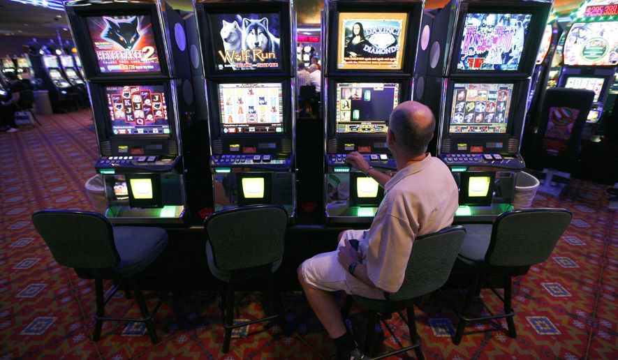 In this June 28, 2011 photo, Lynn Port plays a slot machine at the Royal River Casino in Flandreau, S.D. A long-simmering tax dispute between the Flandreau Santee Sioux Tribe and the state of South Dakota is threatening to shut down alcohol sales at the Royal River Casino and Hotel. (AP Photo/The Argus Leader, Devin Wagner ) NO SALES
