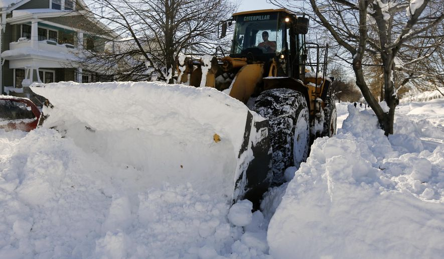 A front loader clears snow from a street in the south Buffalo on Friday, Nov. 21, 2014, in Buffalo, N.Y. A snowfall that brought huge drifts and closed roads in the Buffalo area finally ended Friday, yet residents still couldn't breathe easy, as the looming threat of rain and higher temperatures through the weekend and beyond raised the possibility of floods and more roofs collapsing under the heavy loads. (AP Photo/Mike Groll)