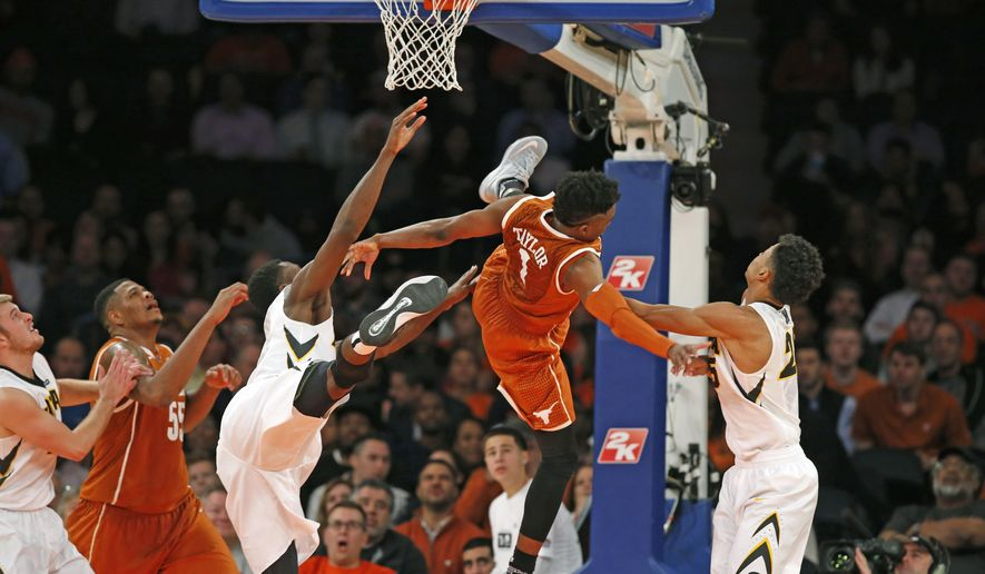 Iowa center Gabriel Olaseni, fouls Texas guard Isaiah Taylor (1), who falls to the ground after he was flagrantly fouled by Olaseni in the second half of an NCAA basketball game at Madison Square Garden in New York, Thursday, Nov. 20, 2014. Texas defeated Iowa 71-57.  (AP Photo/Kathy Willens)