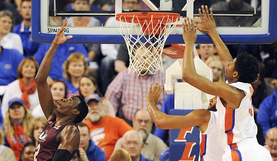 Louisiana-Monroe forward Tylor Ongwae (12) goes over his head to shoot with Florida forward Devin Robinson (3) unable to block during the first half of an NCAA college basketball game in Gainesville, Fla.,  Friday, Nov. 21, 2014. (AP Photo/Phil Sandlin)
