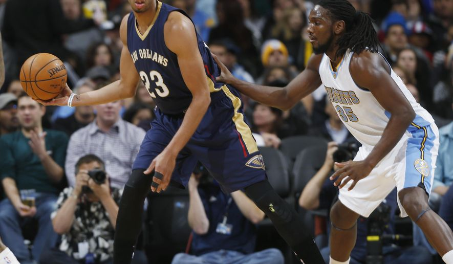 New Orleans Pelicans forward Anthony Davis, left, fields a pass as Denver Nuggets forward Kenneth Faried covers in the first quarter of an NBA basketball game in Denver, Friday, Nov. 21, 2014. (AP Photo/David Zalubowski)