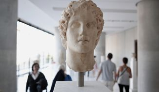 Visitors walk behind an ancient marble head of ancient Greek warrior-king Alexander the Great, displayed at the Acropolis museum in Athens, Oct. 12, 2014. Alexander the Great was one of the world's most successful military commanders, who enlarged his father's kingdom to include an empire stretching from modern Greece to India. During his youth, Alexander was tutored by the ancient Greek philosopher Aristotle until the age of 16. (AP Photo/Petros Giannakouris)