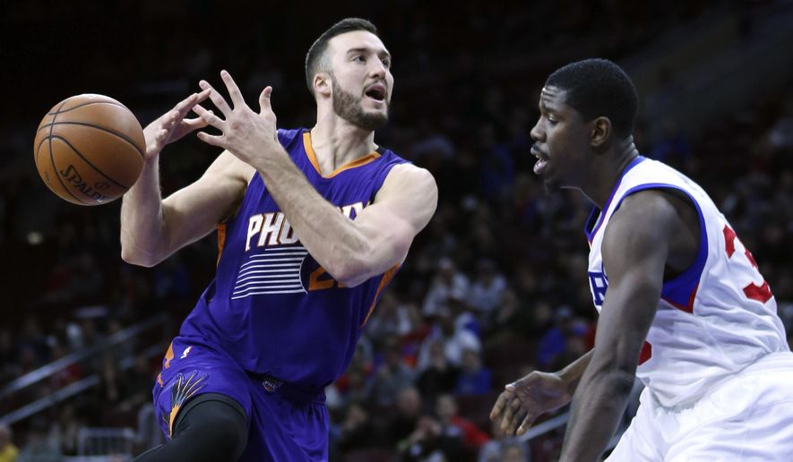 Philadelphia 76ers center Henry Sims, right, stands near after knocking the ball away from Phoenix Suns center Miles Plumlee (22) as he drives to the basket in the first half on an NBA basketball game, Friday, Nov. 21, 2014, in Philadelphia. (AP Photo/Laurence Kesterson)