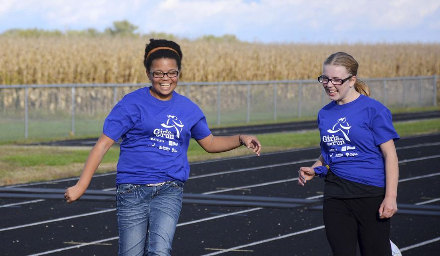 ADVANCE FOR USE SUNDAY, NOV. 23 AND THEREAFTER - In this Oct. 7, 2014 photo, sixth-graders Jasmine Ward, right, and Sierra Cameron finish a lap at practice for the Girls on the Run program in Strasburg, Ill The program, now in it's third year at Stewardson-Strasburg Schools, prepares third through sixth grade students to participate in a 5K. (AP Photo/Effingham Daily News, Jackson Adams)