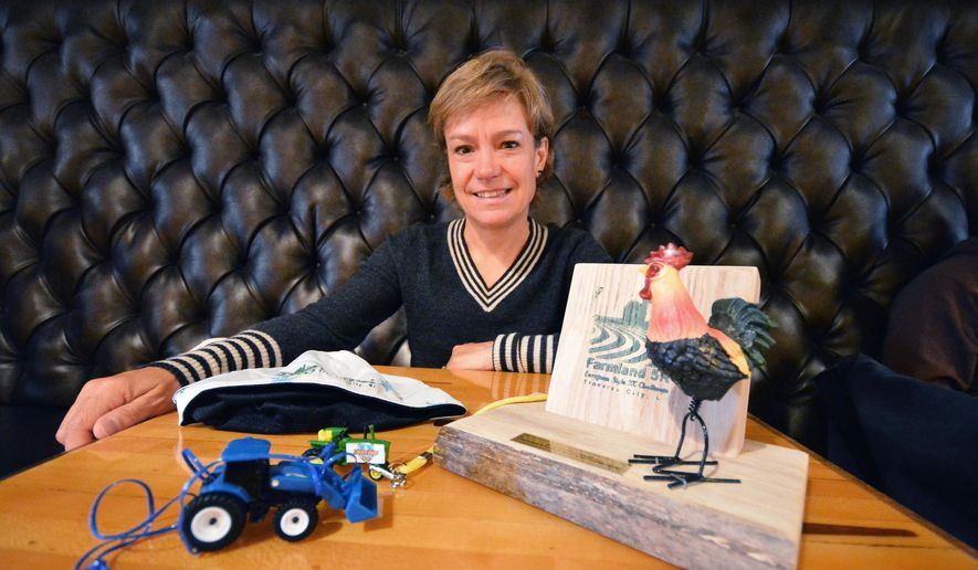 ADVANCE FOR WEEKEND EDITIONS, NOV. 22-24- In a Nov. 6, 2014 photo in Traverse City, Mich., Lisa Taylor, race director of the Farmland 5k race, displays a barnwood trophy from last year's event, right, and tractor toys earned by all finishers at previous events. Like any business, planning an athletic event involves a balance sheet. Income and expenses must fall into line. On the plus side, a running event takes in money from entry fees and sponsors. On the minus side are all the expenses. (AP Photo/Traverse City Record-Eagle, Dan Nielsen) MANDATORY CREDIT