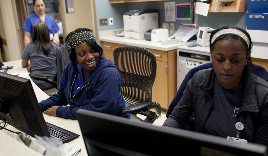 In this Nov. 7, 2014 photo, nurse Shandricka Duffie, left, laughs as she and Shalonda Scott, right, work at a nurses' station in the emergency trauma center at Hurley Medical Center in Flint, Mich. A University of Michigan Injury Center study that was done at Hurley Medical Center found that youth violence should be considered a chronic disease. (AP Photo/The Flint Journal-MLive.com, Laura McDermott) LOCAL TELEVISION OUT; LOCAL INTERNET OUT