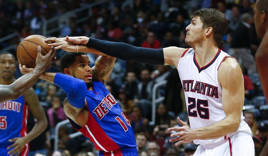 Detroit Pistons guard D.J. Augustin (14) is fouled by Atlanta Hawks guard Kyle Korver (26) in the second half of an NBA basketball game  Friday, Nov. 21, 2014, in Atlanta. Atlanta won 99-89.   (AP Photo/John Bazemore)