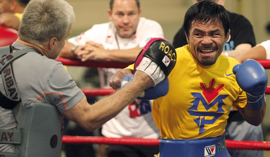 In this Nov. 18, 2014 photo, Philippine boxer Manny Pacquiao, right, trains at the Cotai Arena Gym of the Venetian Resort and Casino in Macau. Pacquiao and Chris Algieri of the United States are scheduled to meet in a title fight on Sunday, Nov. 23, in Macau. (AP Photo/Team Pacquiao, Mike Young) EDITORIAL USE ONLY, NO SALES