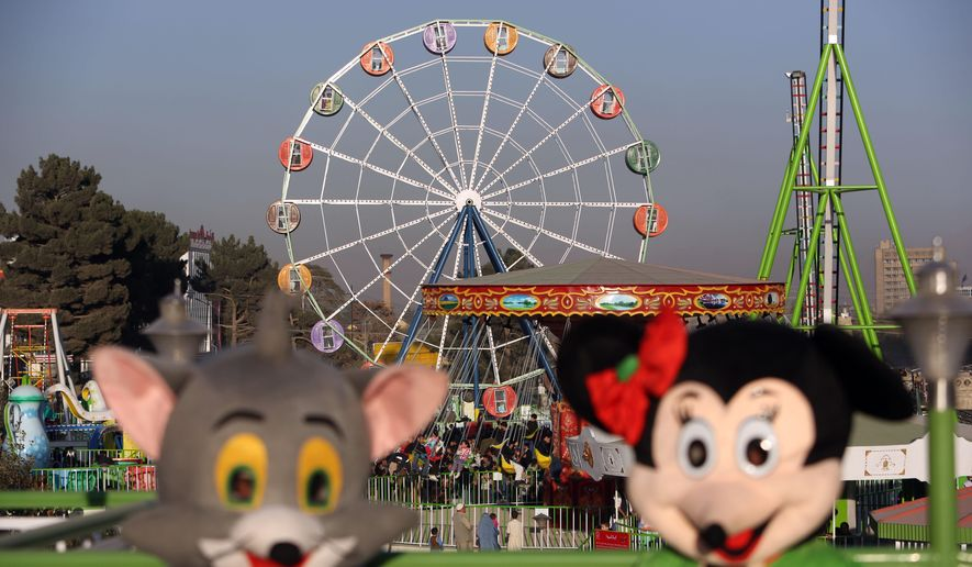 In this Friday, Nov. 14, 2014 photo, friendly characters that looklike Jerry the mouse from Tom and Jerry, left, and Minnie Mouse welcome visitors at Afghanistan's first amusement park called City Park in Kabul. Excitement builds in the queue forming behind the barbed-wire security fence outside the park as children in bright clothes clutch their parents' hands and hop from foot to foot in anticipation of the pleasures waiting behind the high concrete blast walls. For the thousands of families who have visited there since it opened during a national religious holiday weekend in October, it is a rare escape from lives blighted by war, death and misery. (AP Photo/Rahmat Gul)
