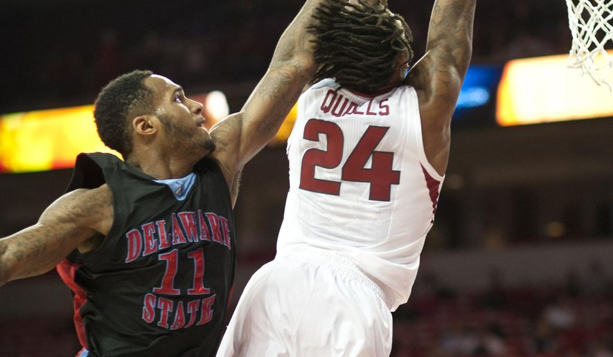 Arkansas' Michael Qualls (24) reaches for the basket as Delaware State's DeAndre Haywood (11) defends in the first half of an NCAA college basketball game in Fayetteville, Ark., Friday, Nov. 21, 2014. (AP Photo/Sarah Bentham)