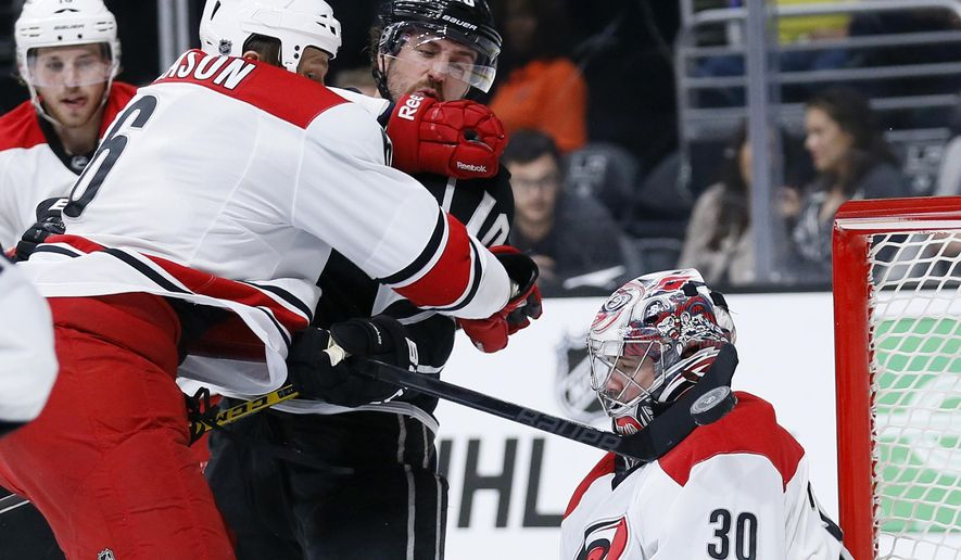 Los Angeles Kings center Mike Richards, center, attempts to score past Carolina Hurricanes goalie Cam Ward, right, as Hurricanes defenseman Tim Gleason, left, helps Ward during the second period of an NHL hockey game, Thursday, Nov. 20, 2014, in Los Angeles. (AP Photo/Danny Moloshok)