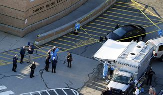 This Dec. 14, 2012, aerial file photo shows officials standing outside of Sandy Hook Elementary School in Newtown, Conn. (AP Photo/Julio Cortez, file) ** FILE **