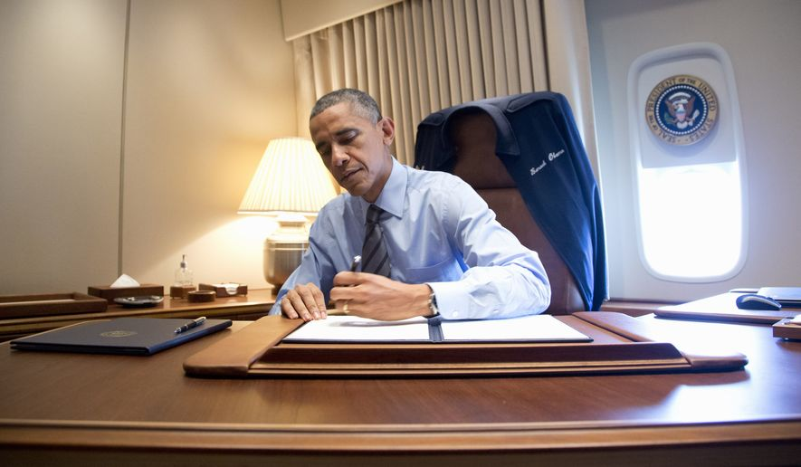 President Barack Obama signs two presidential memoranda associated with his actions on immigration in his office, on Air Force One as he arrives at McCarran International Airport in Las Vegas, Friday, Nov. 21, 2014. The president will travel to Del Sol High School to speaks about the steps he will be taking on immigration. (AP Photo/Carolyn Kaster)