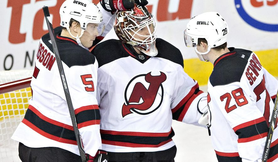 New Jersey Devils' Adam Larsson (5), Cory Schneider (35) and Damon Severson (28) celebrate the team's 2-0 win over the Edmonton Oilers in an NHL hockey game Friday, Nov. 21, 2014, in Edmonton, Alberta. (AP Photo/The Canadian Press, Jason Franson)