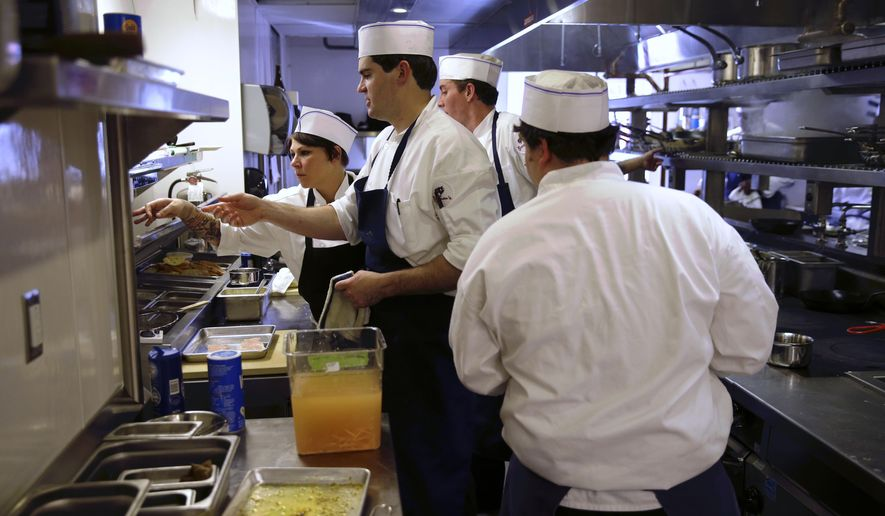 Kitchen staff, including Patrick Brennan, center, son of proprietor Ralph Brennan, prepare dishes during a tasting at Brennan's Restaurant in New Orleans, Friday, Nov. 21, 2014. The historic French Quarter restaurant that closed in 2013 amid financial turmoil and after decades of family strife, re-opens on Tuesday, Nov. 25.  (AP Photo/Gerald Herbert)