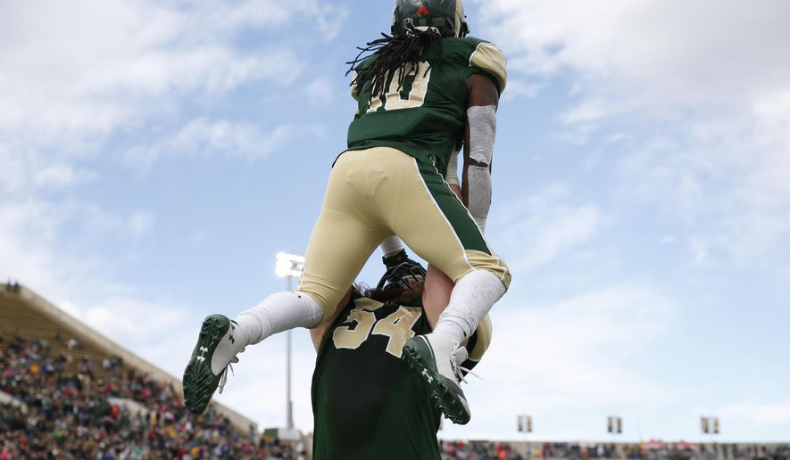 Colorado State offensive lineman Fred Zerblis, bottom, hoists running back Dee Hart into the air after Hart's touchdown against New Mexico in the second quarter of an NCAA college football game in Fort Collins, Colo., on Saturday, Nov. 22, 2014. (AP Photo/David Zalubowski)