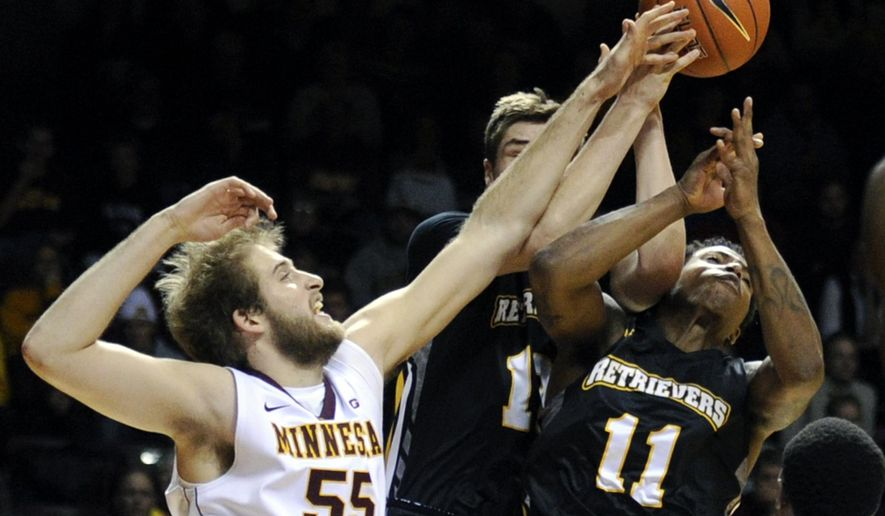 Maryland-Baltimore County guard Will Darley, center, and guard Charles Taylor (11) reach for a rebound with Minnesota center Elliott Eliason (55) during the first half of an NCAA college basketball game Saturday, Nov. 22, 2014, in Minneapolis. (AP Photo/Hannah Foslien)