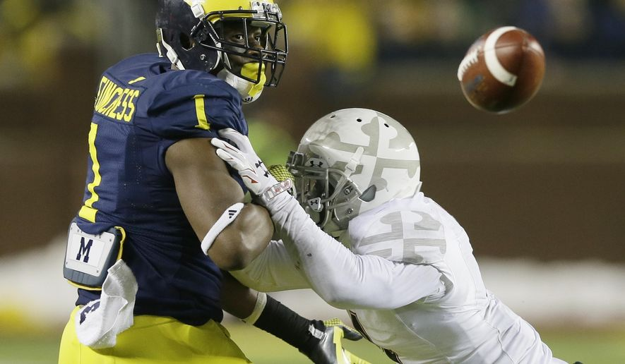 Maryland defensive back William Likely (4) breaks up a pass intended for Michigan wide receiver Devin Funchess (1) during the second half of an NCAA college football game in Ann Arbor, Mich., Saturday, Nov. 22, 2014. (AP Photo/Carlos Osorio)
